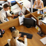 high angle view of a businessman and two businesswomen working in an office --- Image by © Royalty-Free/Corbis